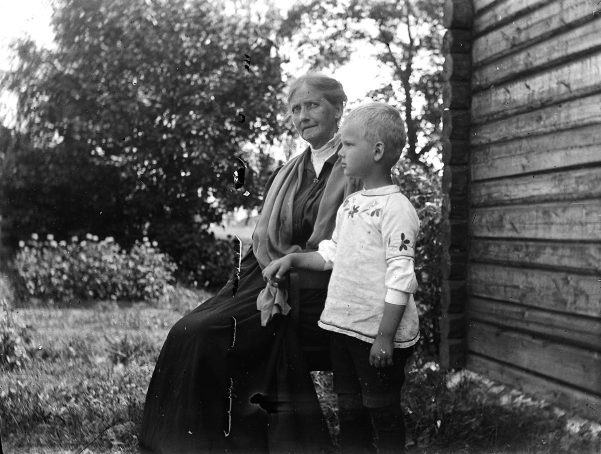 Kvinne med barnebarn i husveggen i Kvalstua, Helgøya. Anne (Eliesson) Dybwad og Wilhelm Dybwad.