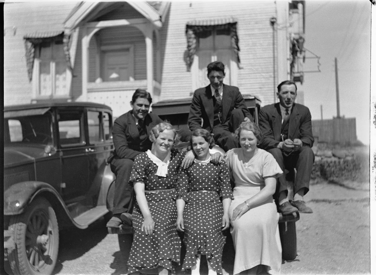 Tre menn og tre kvinner sitter på en bil , muligens en Buick 1926-1928,(Samme situasjon HHB-00919). Den skjulte bilen er bil D-82, en Auburn fra 1925-27. Bildet antas å være fra andre halvdel av 1930-tallet, siden bilnummeret var i bruk på en/flere Ford'er i registreringsbøkene fra 1925, 27, 28, 30 og 35 (Hamar politidistrikt, Vang eller Løten).