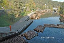 Fra Hølen, nedenfor Løveid sluser i Skiensvassdraget.  Fotografiet viser en båt som brukes til å trekke sammen tømmer, som nettopp har kommet ned gjennom slusene.  Slusekamrene hadde bare plass til lenker med fem og fem bunter.  I Hølen ble disse enhetene koplet sammen igjen i lenker på tjue bunter, som ble trukket inn mot land og forankret der.  Derfra ble de hentet med en slepebåt, to og to kjeder a tjue bunter av gangen.  I bakgrunnen skimtes kirka og skolen på Løveid i et landskap med glissen skog.