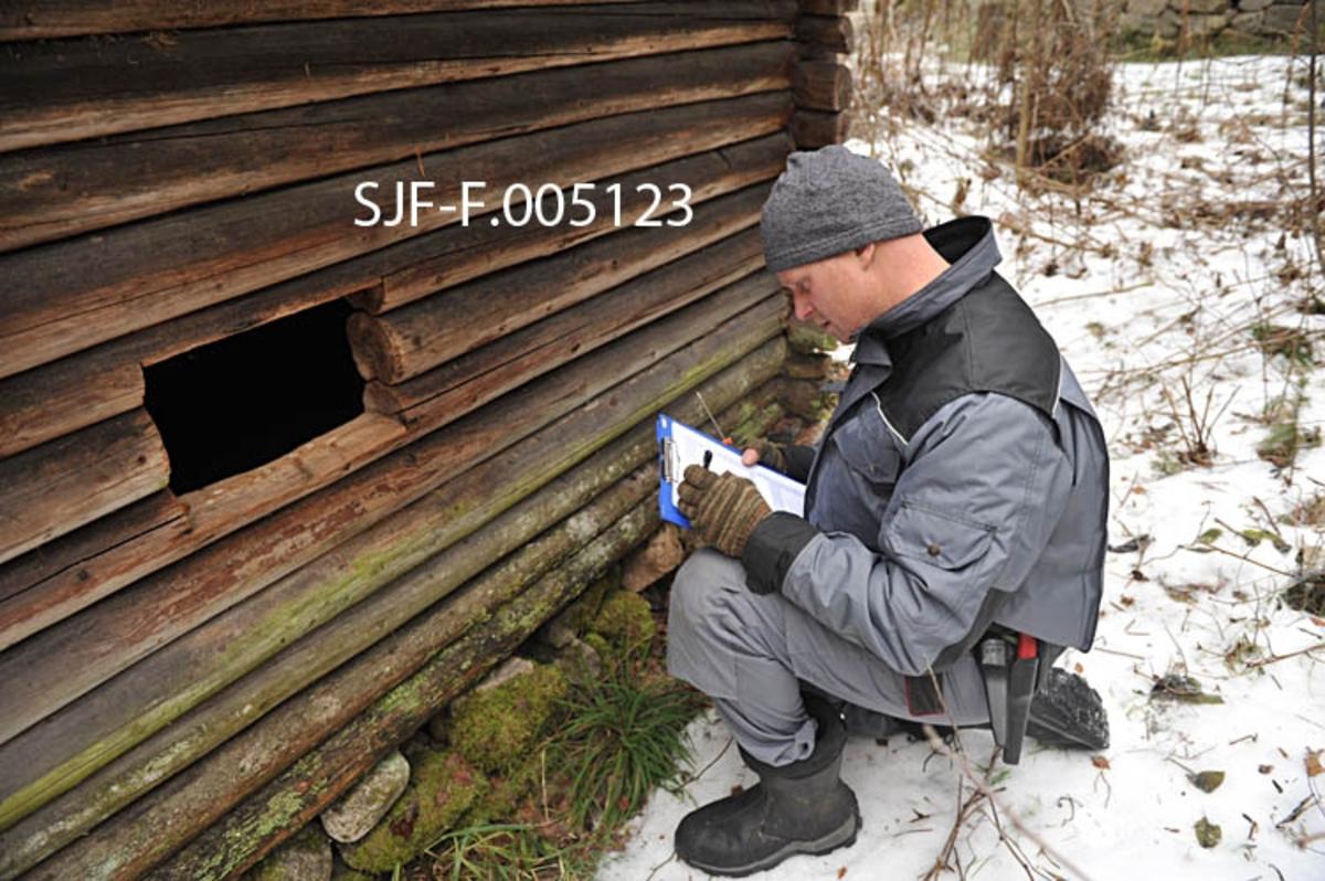 Tømrer Knut-Arild Nordli undersøker en skogsstall fra Sørskogbygda i Elverum [SJF-B. 0014] i Norsk Skogmuseums friluftsmuseum på Prestøya.  Nordli sitter på huk ved på sørsida av bygningen, der han gjør notater om fundament og fukteksponering på den nedre delen av lafteveggen.  Tømreren er kledd i grå arbeidsdress med svarte skulderstykker, og har grå lue på hodet.  Våren 2012 ble Nordli engasjert for å gjennomgå de antikvariske bygningene i Hedmark fylkesmuseum med sikte på å definere materialbehov og tidsforbruk ved restaureringstiltak ved fylkesmuseets åtte avdelinger.  Vurderingsarbeidet i Skogmuseets friluftsmuseum ble utført seinhøstes 2012.