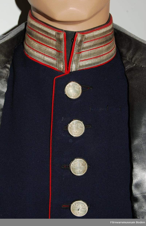 Mörkblått kläde med rött foder och passpoaler. Krage med broderade knapphålsgaloner i silver. Inga gradbeteckningar eller axelklaffar monterade. Framtill enkel rad med 8 knappar av regementets modell i silver.