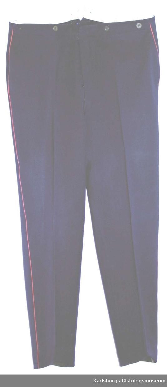 Långbyxa m/1886 i mörkblått kläde. Midjeband med knappar för hängslen . Gylf med knappar o hyska. En bakficka. På byxbenens sidsömmar rött fyrkantssnöre.