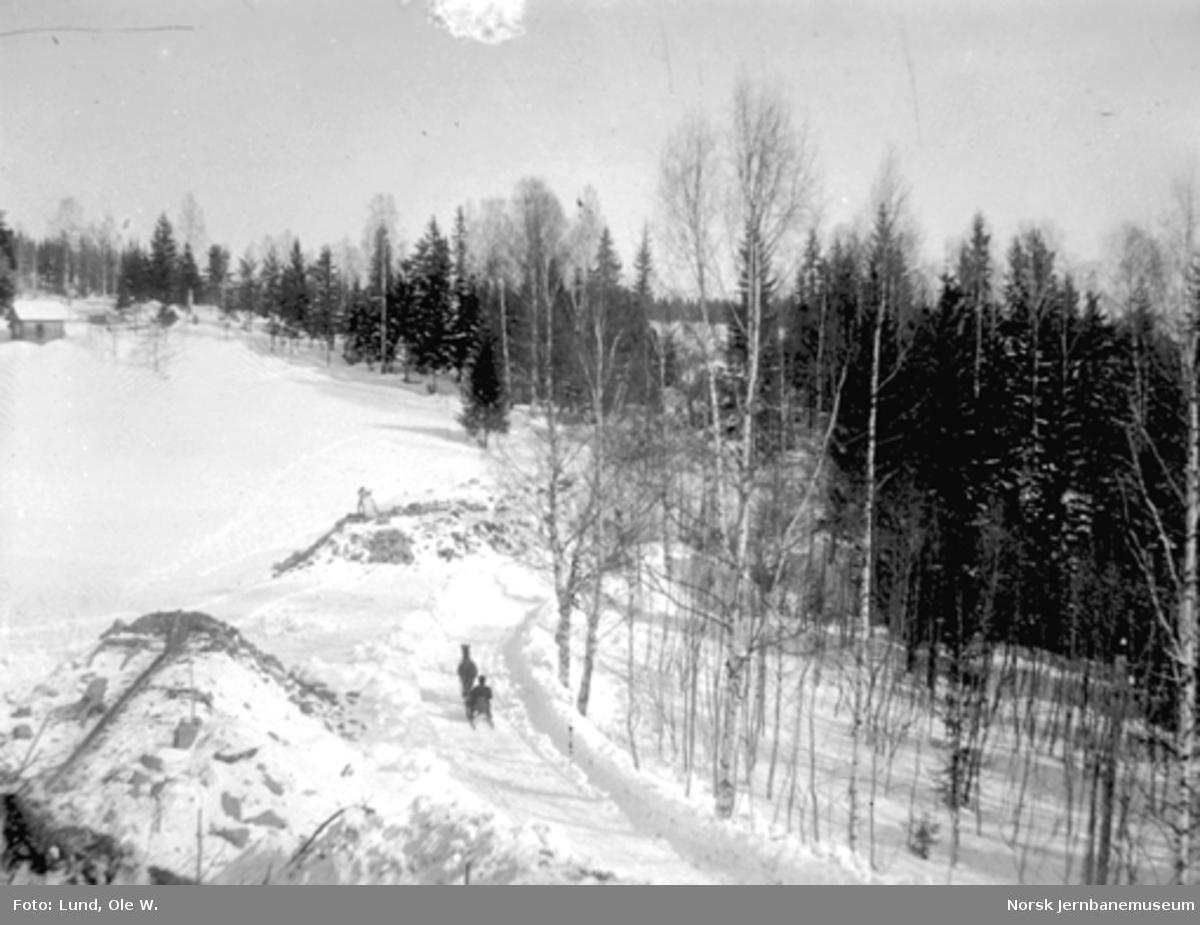 Fra anlegget av Holmestrand-Vittingfossbanen : vinterbilde med mann med trillebår på en fylling mellom Haslestad og Kleppan mens en mann med hest og slede passerer på landevegen