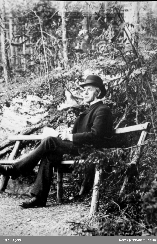 Carl Abraham Pihl sittende på en benk