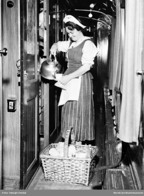 En togvertinne serverer kaffe fra kaffekjel i sovevognkorridor