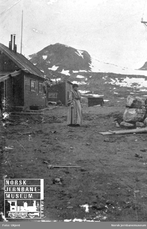 Anleggsbrakke på Finse med en kvinne utenfor