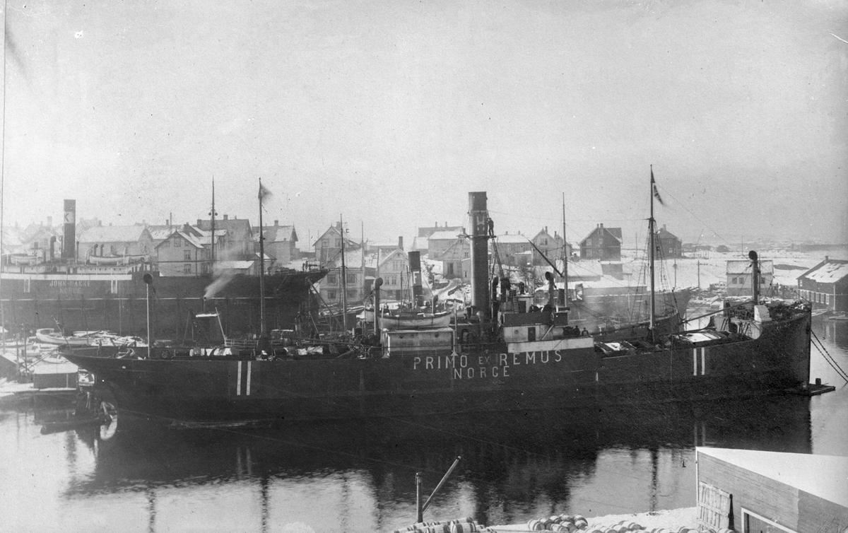 """Dampskipet D/S """"Primo"""" ankret opp  ved Smedasundet in Haugesund. Trehus, stort skp og mindre båter i bakgrunnen."""