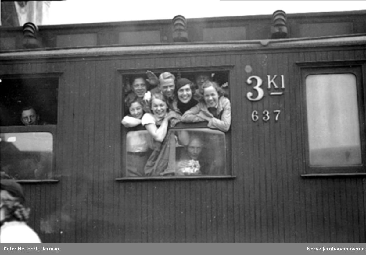 Reisende i vinduet på en personvogn på Oslo Østbanestasjon
