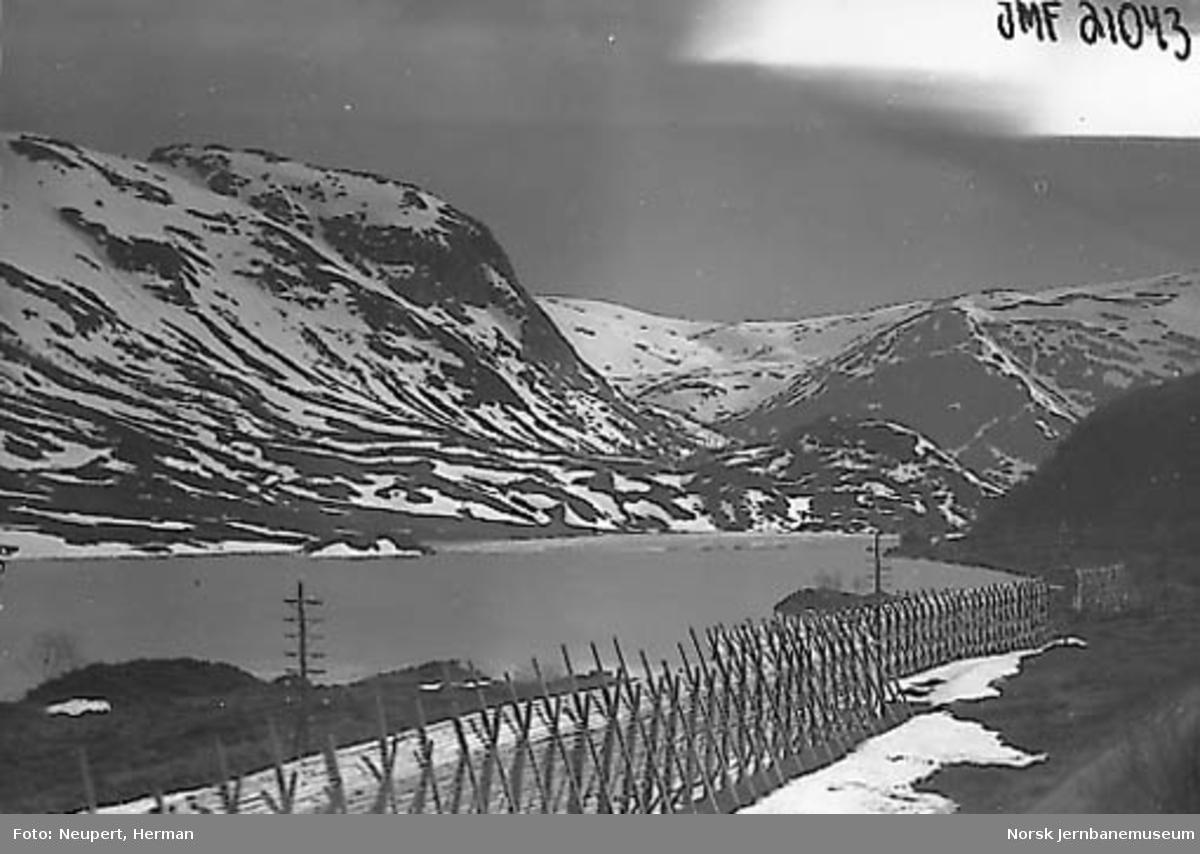Utsikt fra toget like ved Vieren vokterbolig, sett vestover mot Langevatten (hvor Langevassosen vokterbolig ligger på odden)