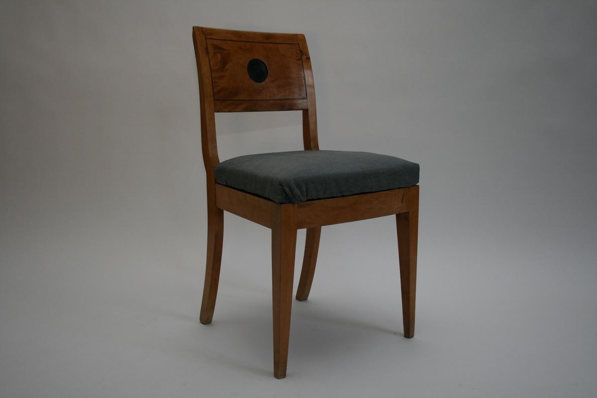 Empirestol i bjørk, glatt ryggbrett med innlagte liner i svart, og et svart nedsenket sirkelformet felt i midten. manglende messingkapsel. Setet trukket med blått ulltrekk En av to like stoler.
