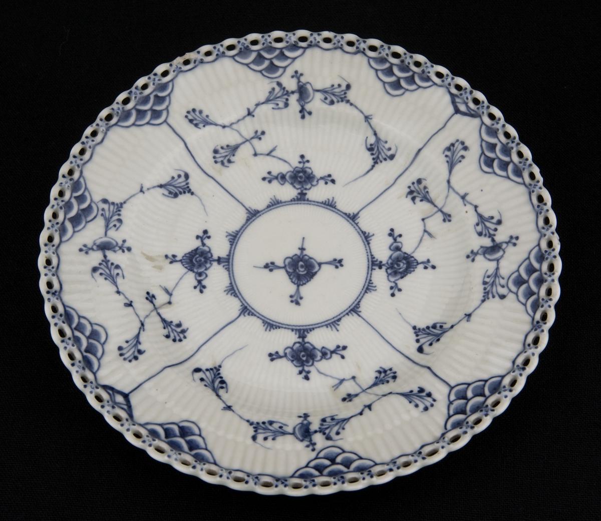 Flat spisetallerken i riflet gods med blått musselmalt mønster og gjenombrudt blondekant. Fabrikkmerket med Royal Copenhagens tre bølger samt malersignatur