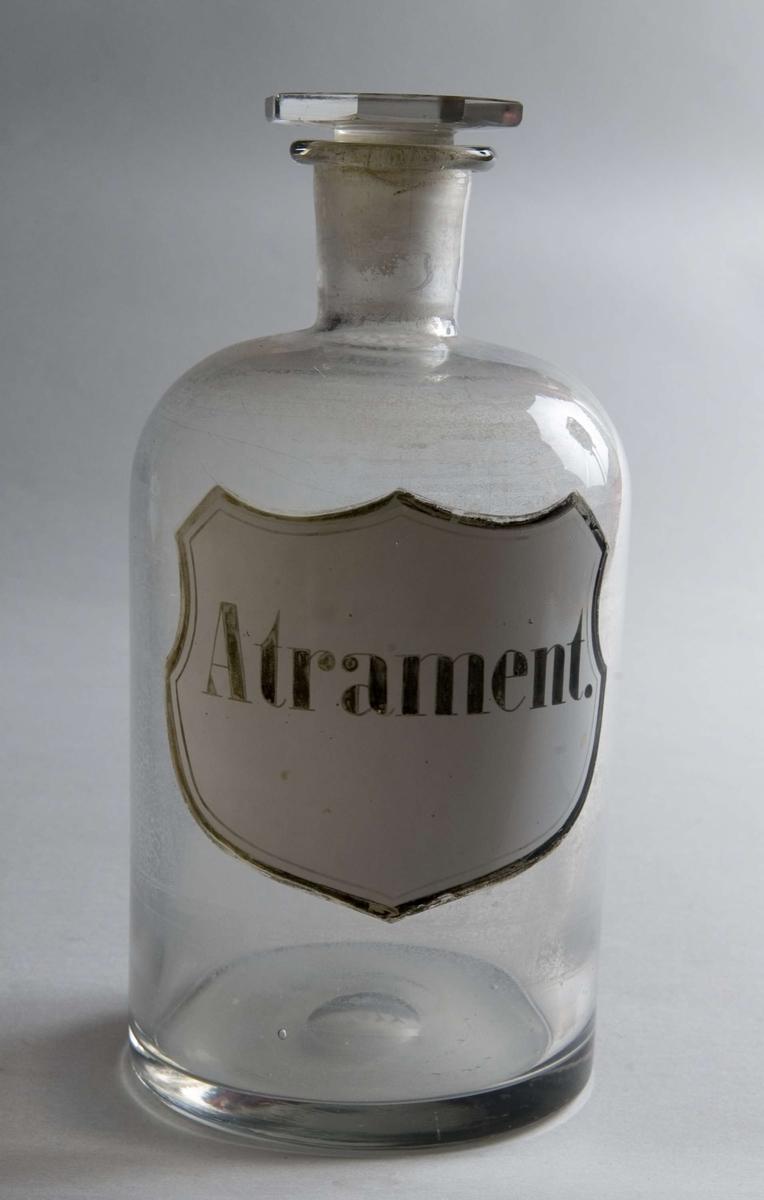 Standglass med propp. Hvit skjoldformet etikett med svart skrift og gullfarget ramme. Emaljert.