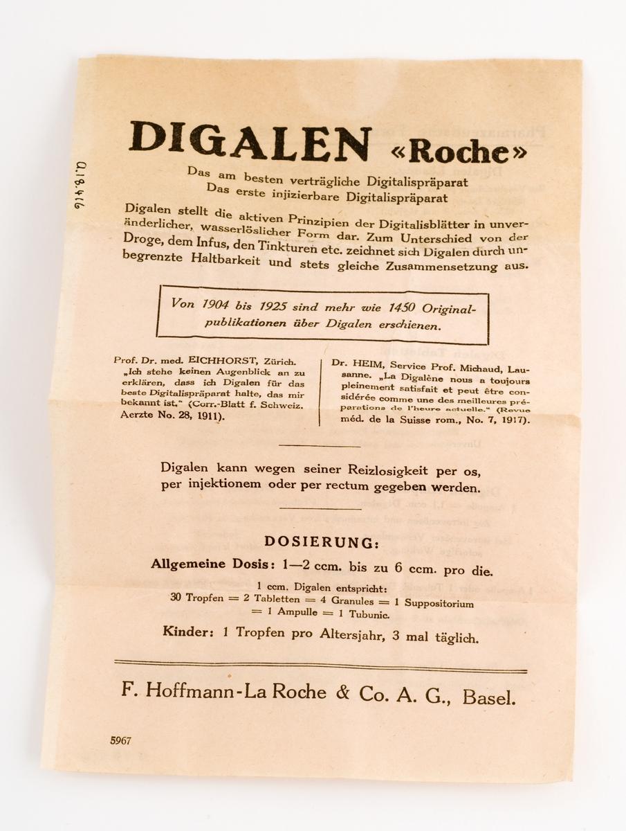 """Brun medisinflaske med rød gummipropp. Pålimt hvir papiretikett med rød og blå skrift.  7-sifret tall stemplet på etiketten (produksjonsnummer) Flasken er tom.  Løst pakningsvedlegg med info om diverse preparater med samme spesialitetsnavn DIGITALEN """"Roche""""."""