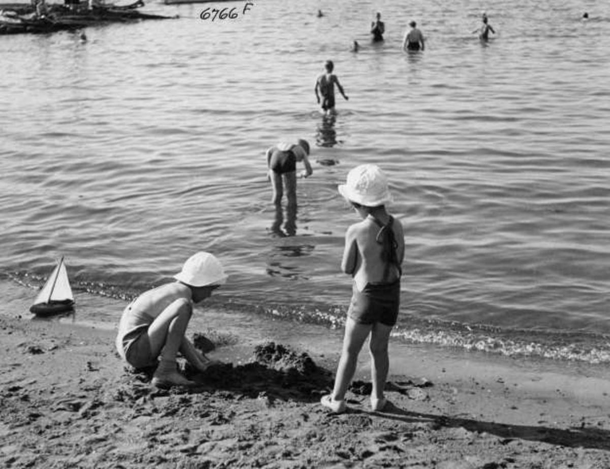 Strandliv med badegjester  ved sjøen på Ingierstrand bad utenfor Oslo. Barn leker i sanden.