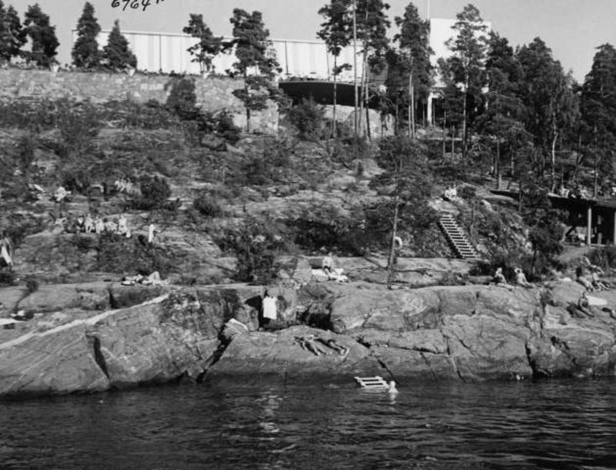 Strandliv med badegjester som soler seg på svaberget ved sjøen på Ingierstrand bad utenfor Oslo. Restauranten i bakgrunnen.