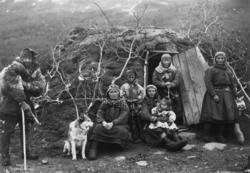 Svenske samer og en hund utenfor døråpningen til en gamme, f
